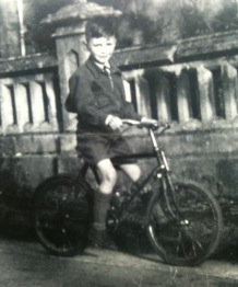 Childhood portrait of Roger Symonds with bike