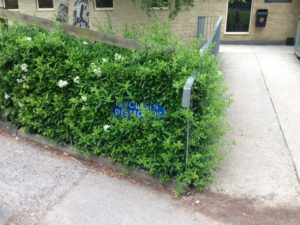 Obscured Cyclists dismount sign in Monkton Combe School